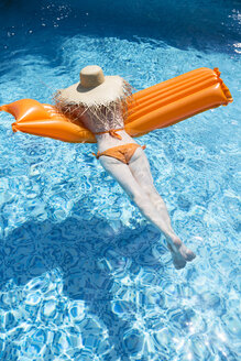 Back view of woman relaxing on orange airbed in swimming pool - MAEF12350