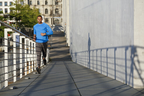 Young man running on footbridge in the city - FKF02431