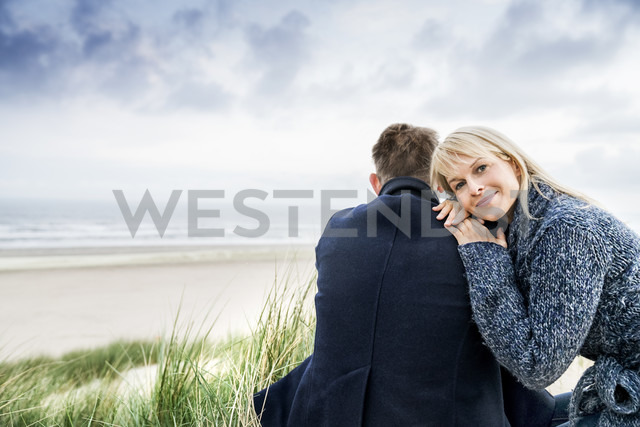Couple sitting in dunes - FMKF04204
