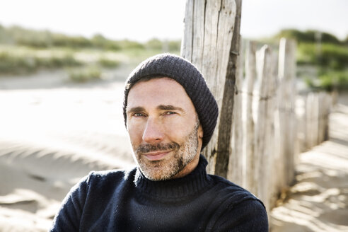 Portrait of smiling man at fence on the beach - FMKF04213