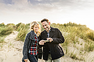 Happy couple in dunes sharing cell phone - FMKF04231
