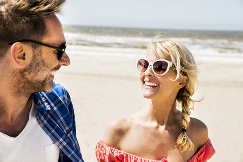 Happy couple wearing sunglasses on the beach - FMKF04237