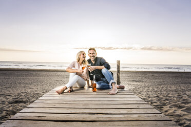 Happy couple with wine glasses sitting on boardwalk on the beach at sunset - FMKF04240