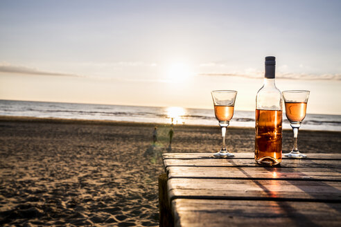 Wine bottle and glasses on boardwalk on the beach at sunset - FMKF04243