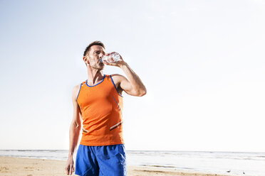 Athlete drinking from bottle on the beach - FMKF04246