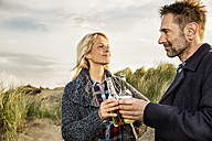 Smiling couple in dunes clinking beer bottles - FMKF04249