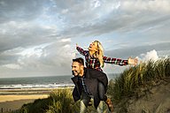 Happy playful couple in dunes - FMKF04252