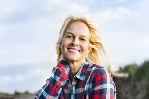 Portrait of smiling woman in dunes - FMKF04255