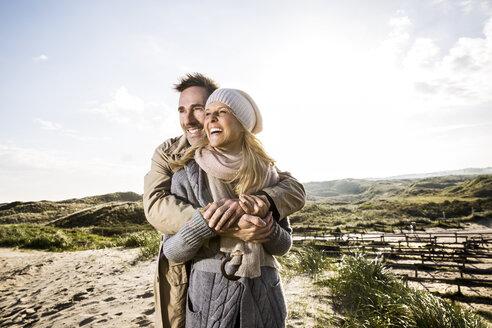 Happy couple hugging in dunes - FMKF04264