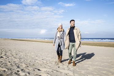 Couple in warm clothing walking on the beach - FMKF04267