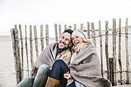 Happy couple wrapped in blanket on the beach - FMKF04276