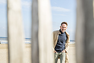 Portrait of smiling man on the beach - FMKF04279