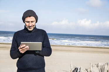 Man using tablet on the beach - FMKF04282