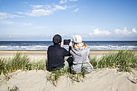 Couple sitting in dunes on the beach with tablet - FMKF04285