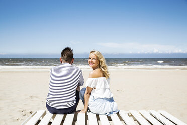 Couple sitting on boardwalk on the beach - FMKF04291