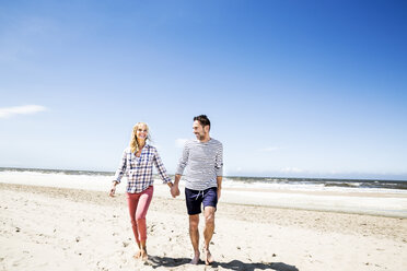 Couple walking hand in hand on the beach - FMKF04294
