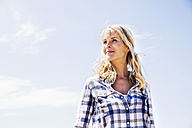 Blond woman wearing checked shirt outdoors - FMKF04297