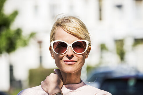 Portrait of blond woman wearing sunglasses - FMKF04306