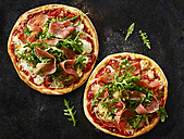 Pizza with ham and rocket on dark ground - KSWF01827
