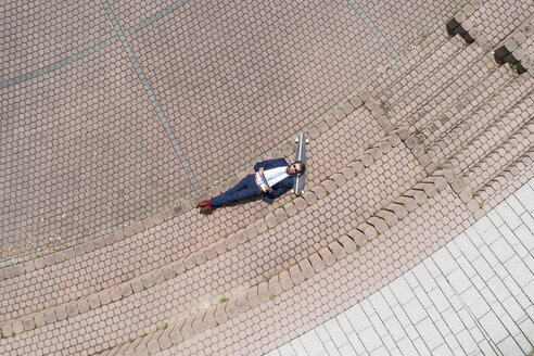 Businessman with skateboard lying on a wall using tablet and headphones - MAEF12359