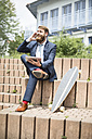 Businessman with skateboard, tablet and earphones on the phone - MAEF12362