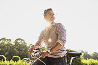 Man with bicycle in a park at sunrise - DIGF02557