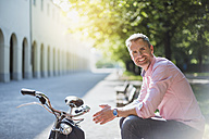 Portrait of smiling man with bicycle sitting on a park bench - DIGF02569