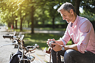 Smiling man with bicycle looking at old-fashioned camera on a park bench - DIGF02572