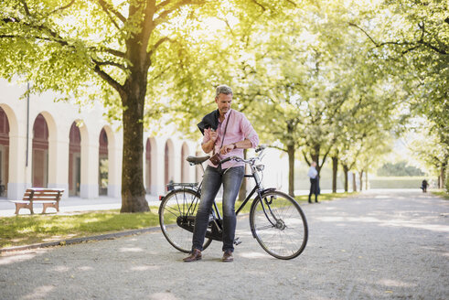 Man with bicycle in a park having a break - DIGF02575