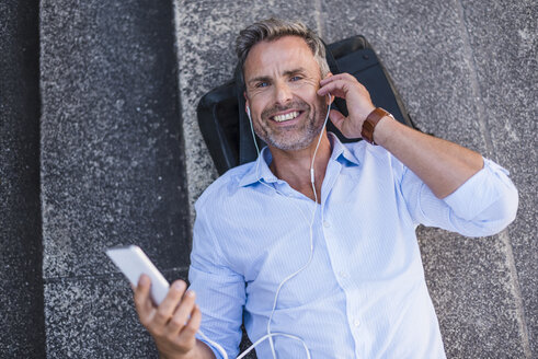 Smiling man lying on stairs with cell phone and earbuds - DIGF02590