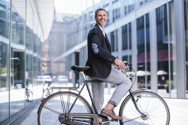 Smiling businessman on bicycle in the city - DIGF02596