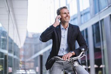 Smiling businessman with bicycle on cell phone in the city - DIGF02599