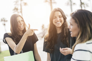 Three friends with shopping bags talking - GIOF02955