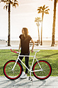 Smiling young woman with fixie bike - GIOF02958