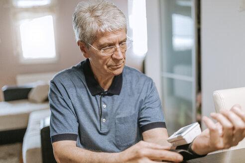 Senior man taking his blood pressure - ZEDF00745