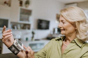 Smiling senior woman taking her blood pressure - ZEDF00754