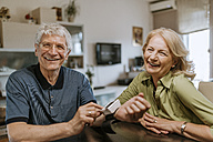 Smiling senior couple with blood pressure gauge - ZEDF00757