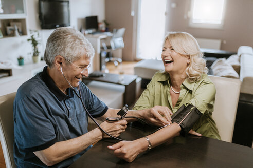 Happy senior couple taking blood pressure - ZEDF00763