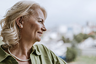Smiling senior woman with hearing aid outdoors - ZEDF00766