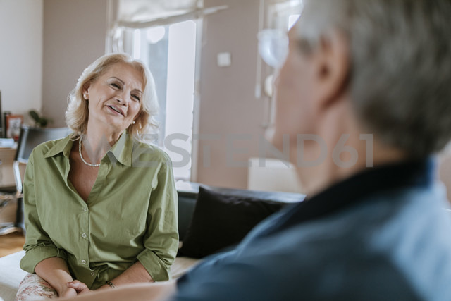 Senior couple at home talking on couch - ZEDF00769