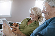 Happy senior couple at home sitting on couch using tablet - ZEDF00778