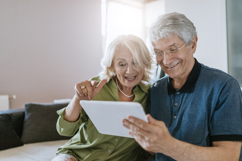 Happy senior couple at home sitting on couch sharing tablet - ZEDF00781