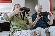 Senior couple at home sitting on couch holding VR glasses - ZEDF00784
