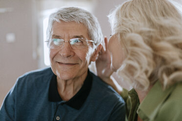 Senior woman talking to husband with hearing aid - ZEDF00787