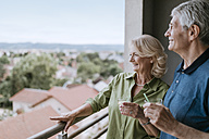 Smiling senior couple on balcony looking at view - ZEDF00790