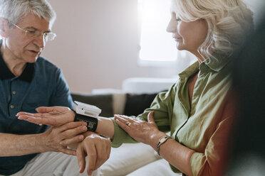 Senior couple taking blood pressure at home - ZEDF00796