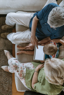 Grandparents and grandson at home sitting on couch sharing tablet - ZEDF00799