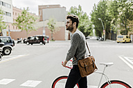 Young man pushing his bike on a street - GIOF02963