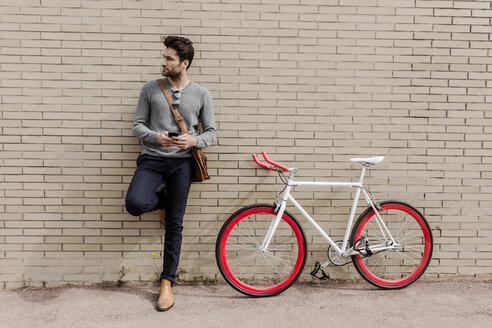 Portrait of young man with racing cycle and cell phone leaning against wall - GIOF02966