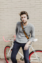 Portrait of young man with racing cycle and headphones - GIOF02969